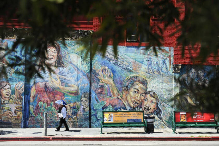 A pedestrian passes by a mural in Boyle Heights.