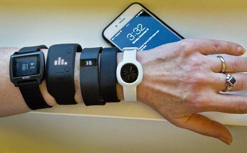 FILE - In this Dec. 15, 2014, file photo, fitness trackers, from left, Basis Peak, Adidas Fit Smart, Fitbit Charge, Sony SmartBand, and Jawbone Move, are posed for a photo next to an iPhone, in New York. Although sales of fitness trackers are strong, many of their owners lose enthusiasm for them on