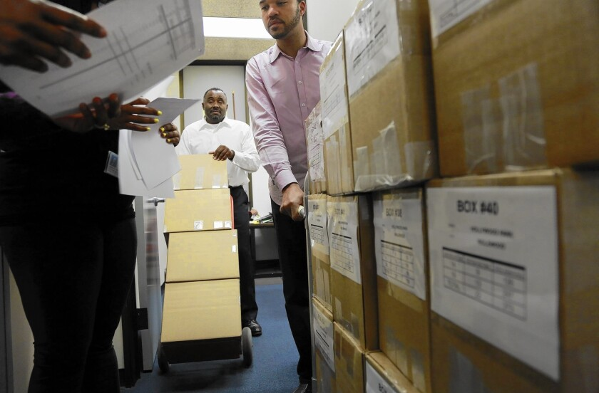 Gerard McCallum, center, and D'Artagnan Scorza, right, both with the City of Champions Revitalization Initiative, deliver 42 boxes containing petitions with 22,000 signatures to the Inglewood city clerk's office Monday.