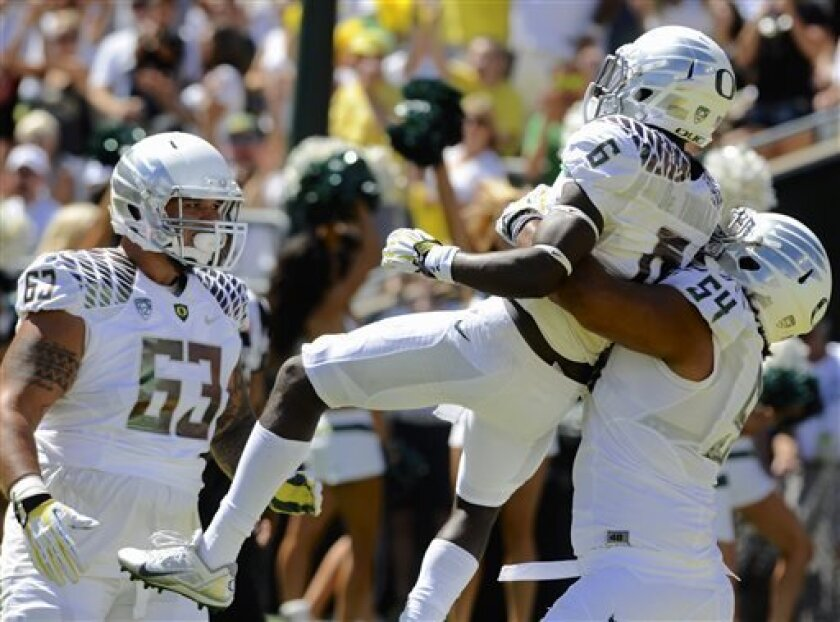 Oregon's De'Anthony Thomas (6) celebrates his touchdown with teammates Hamani Stevens (54) and Mana Craig (63) against Nicholls Stateduring the first half of an NCAA college football game in Eugene, Ore., Saturday, Aug. 31, 2013. (AP Photo/Greg Wahl-Stephens)