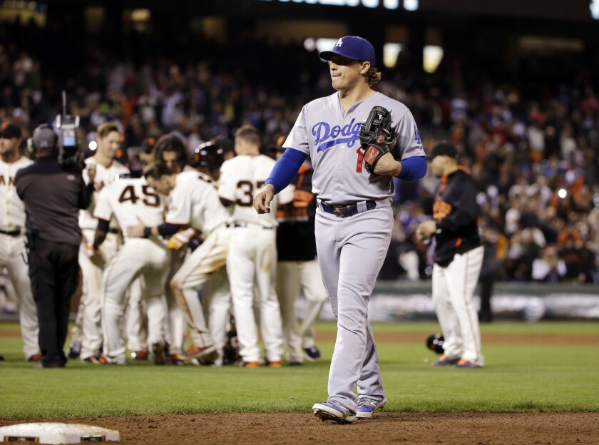 Dodgers' Enrique Hernandez walks off the field as the San Francisco Giants' celebrate a walk-off 3-2 in the 12th inning on Monday night.