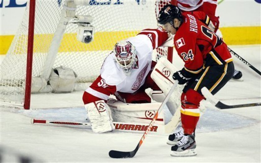 Detroit Red Wings goalie Jonas Gustavsson, left, from Sweden, keeps a close eye on Calgary Flames' Jiri Hudler, from the Czech Republic,  during the second period of an NHL hockey game in Calgary, Alberta, Wednesday, March 13, 2013. (AP Photo/The Canadian Press, Jeff McIntosh)