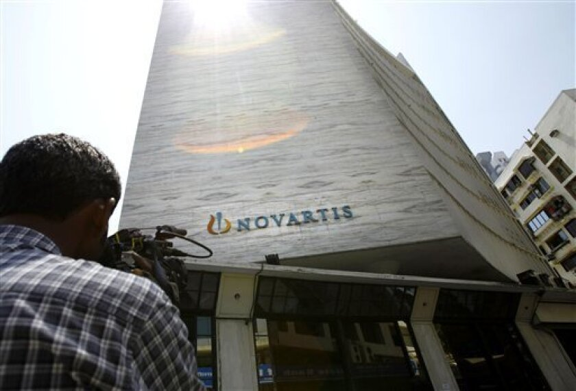 A cameraman films the head office of Novartis India Limited in Mumbai, India, Monday, April 1, 2013. India's Supreme Court on Monday rejected drug maker Novartis AG's attempt to patent a new version of a cancer drug Glivec, in a landmark decision that healthcare activists say ensures poor patients