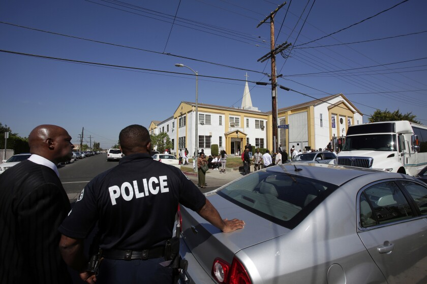Los Angeles police officers watch over a funeral in Compton in October.