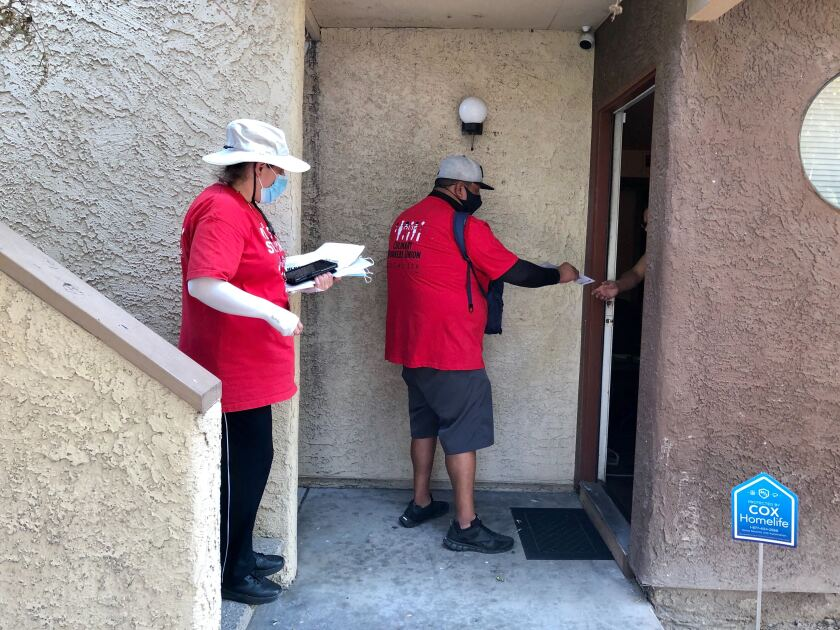 Two people in red shirts hand a pamphlet to a voter through their door
