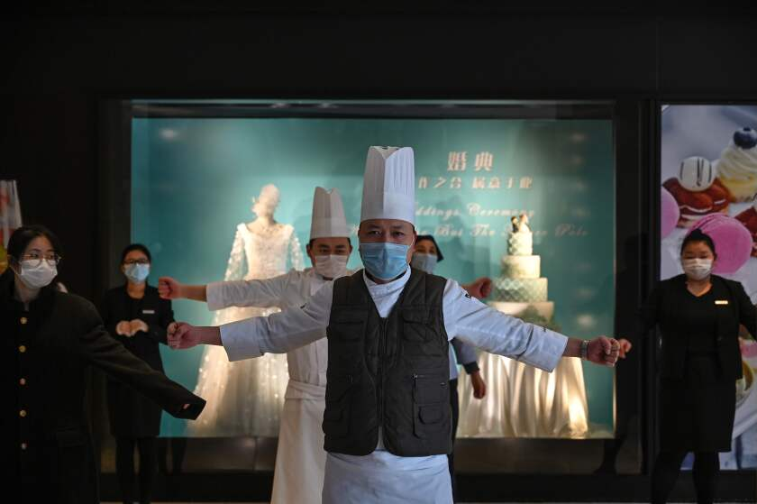Wuhan hotel workers exercise in the lobby during a staff briefing about how to implement new health regulations.