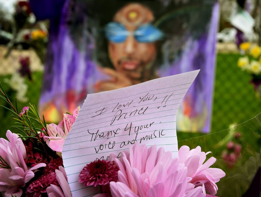 A Prince fan holds flowers outside the Paisley Park compound in Minneapolis on April 22, 2016. Prince died April 21, 2016.