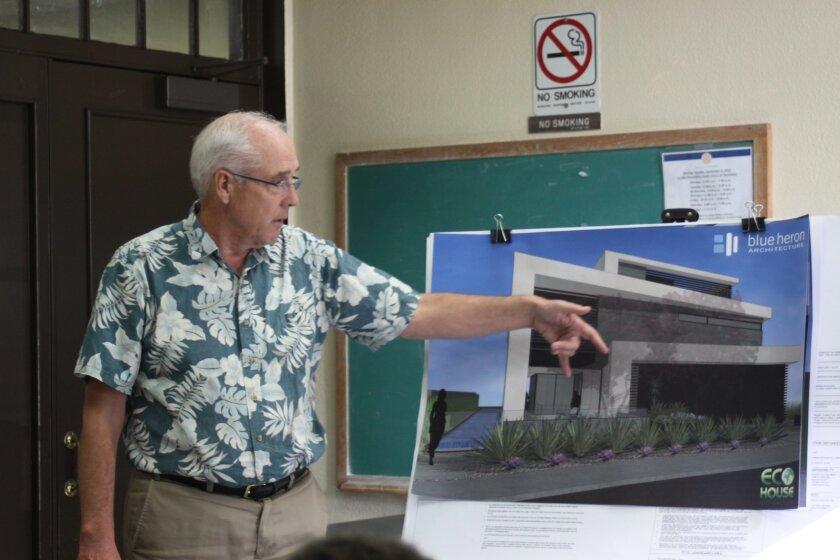 DPR chair Paul Benton examines renderings for the Sea Ridge Drive project.