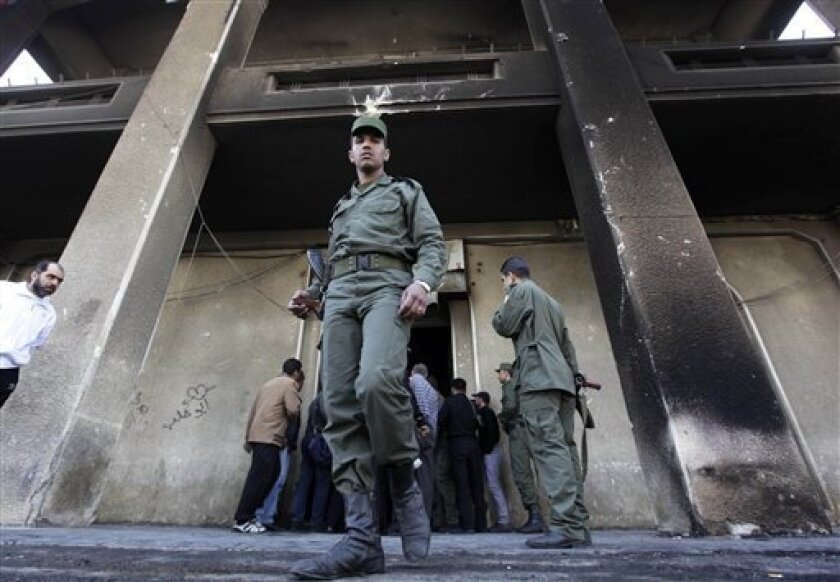 In this March 21, 2011 photo, Syrian army soldier steps out from the burned court building that was set on fire by Syrian anti-government protesters, in the southern city of Daraa, Syria. Unlike the armies of Tunisia and Egypt, Syria's military will almost certainly stand by the country's leader as President Bashar Assad faces down an extraordinary protest movement. (AP Photo/Hussein Malla)