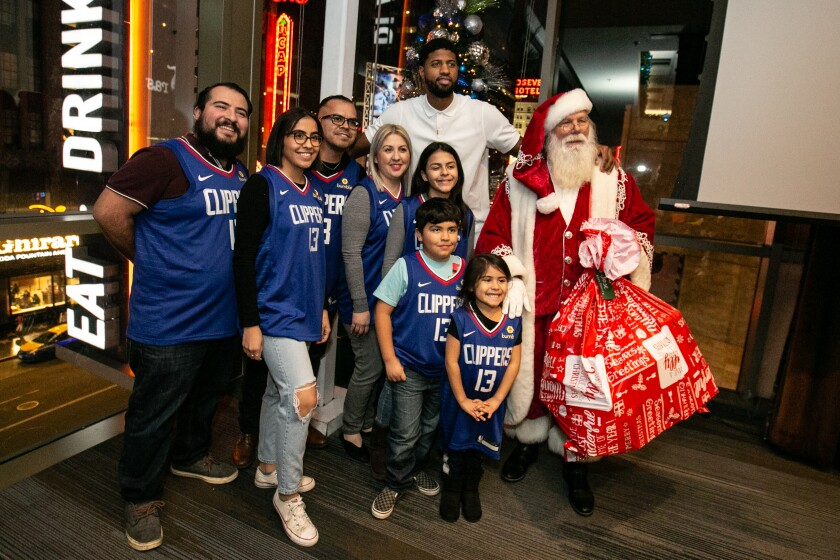 Paul George and Santa take a photo with the Rios family.