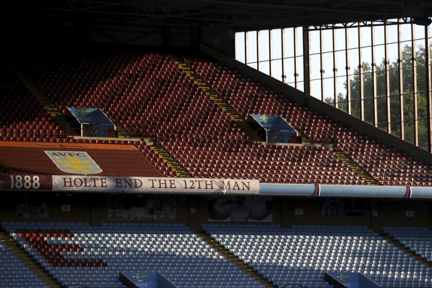 FILE - In this Monday, Sept. 21, 2020 file photo, the sun illuminates the empty stands before the English Premier League soccer match between Aston Villa and Sheffield United at the Villa Park stadium in Birmingham, England. Every empty seat in a Premier League stadium represents a visual reminder of the financial struggle many soccer teams are facing amid the coronavirus pandemic. For smaller soccer teams without TV contracts and huge fan bases, empty seats at matches amid the pandemic can have devastating financial implications. (Tim Goode/Pool via AP, File)