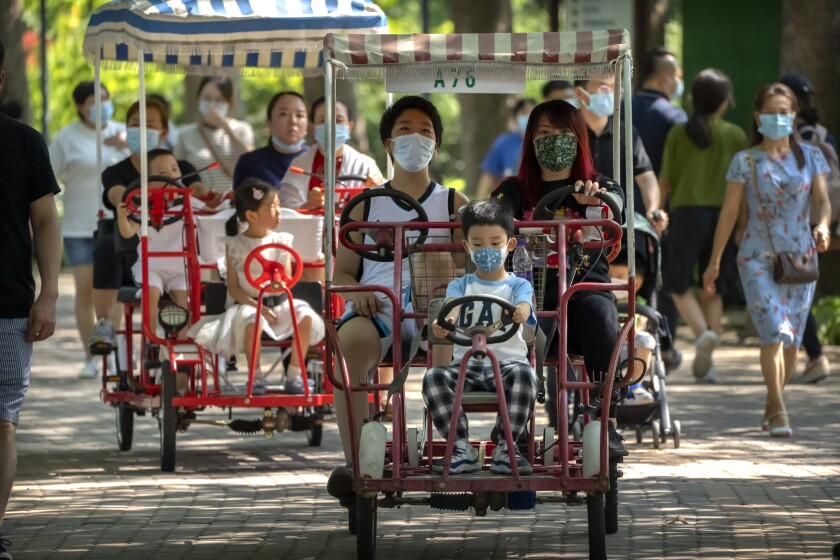 Adults and children ride pedal cycles at a park in Beijing