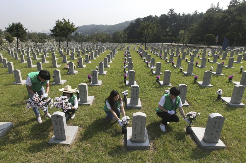 Volunteers place flowers at the graves of fallen soldiers who died in the Vietnam War to celebrate upcoming the Chuseok, the Korean version of Thanksgiving Day, at National Cemetery in Seoul, South Korea, Tuesday, Sept. 22, 2015. It is customary for most Koreans to visit their ancestors' graves on the occasion of Chuseok, one of the two most prominent holidays along with Seol, the Lunar New Year holiday.(AP Photo/Ahn Young-joon)