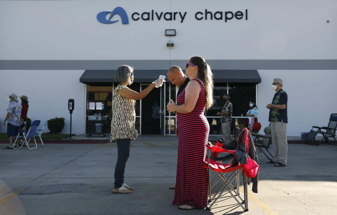 Worshipers John and Kimberly Wellons, right, get their temperature taken by Julie Hamilton at Calvary Chapel Temecula Valley.