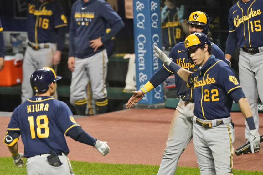 Milwaukee Brewers' Keston Hiura (18) is congratulated by teammates after hitting a two-run home run in the eighth inning in a baseball game against the Cleveland Indians, Friday, Sept. 4, 2020, in Cleveland. (AP Photo/Tony Dejak)