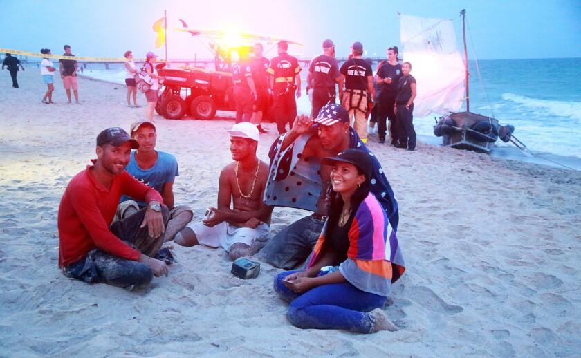 """Cinco de los seis migrantes cubanos que llegaron a la orilla en Lauderdale By-The-Sea descansan en la playa el lunes 6 de junio de 2016. Un grupo de inmigrantes cubanos, incluyendo a una mujer embarazada, llegaron el lunes al sur de Florida a bordo de una embarcación improvisada a la que nombraron """"Barack Obama"""". La prensa local reporta que la mujer fue trasladada al hospital el lunes por la noche para su observación, mientras que otros inmigrantes esperaron en la playa para hablar con los agentes de la Aduana y la Patrulla Fronteriza. (Carline Jean/South Florida Sun-Sentinel via AP)"""