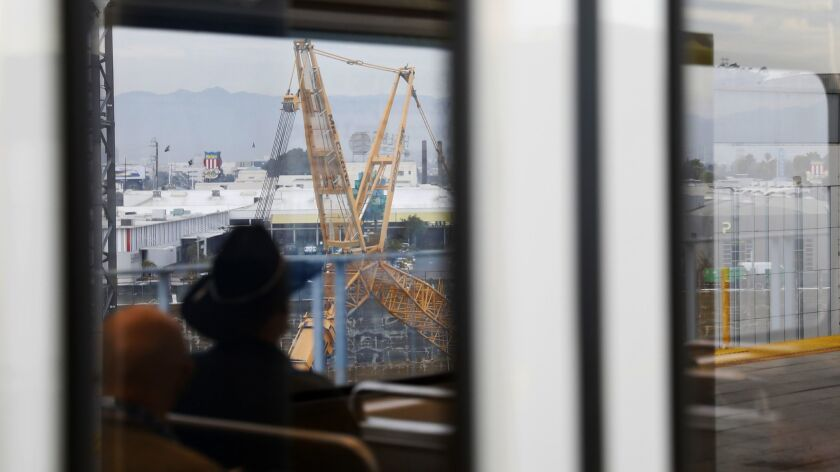 Construction is seen through a window as Metro passengers pass through Culver City in January 2018.