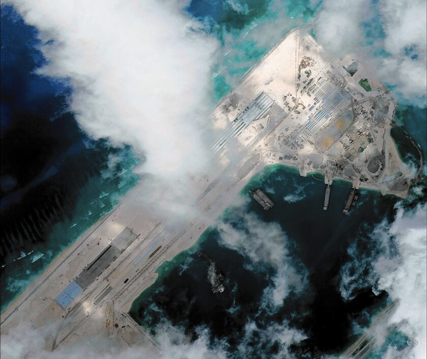 A satellite image shows an airstrip under construction at Fiery Cross Reef in the South China Sea. A U.S. Navy plane flying nearby received eight warnings from the Chinese military.