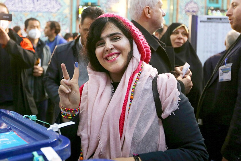 A voter displays her ink-stained finger at a polling station in Tehran on Friday.