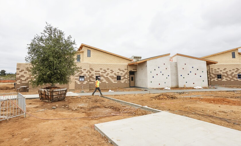 A worker crosses an outdoor area at the new Youth Transition Campus in San Diego.