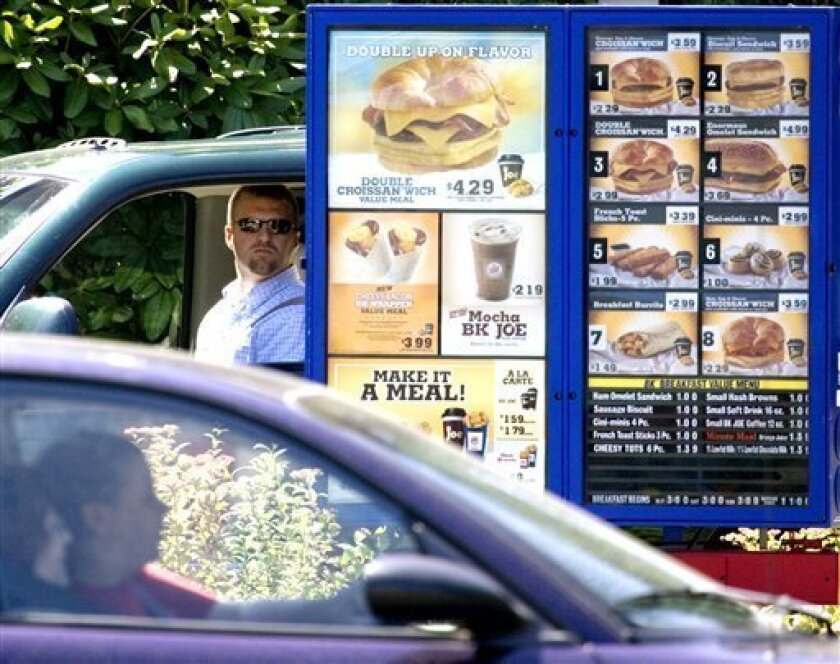 FILE - In this July 31, 2008 file photo, customers view the menu in the drive through line at a Burger King in Portland, Ore., Like it or not, many restaurant diners will soon know more about what they are eating under menu labeling requirements proposed Friday by the Food and Drug Administration. The requirements will force chain restaurants with 20 or more locations, along with bakeries, grocery stores, convenience stores and coffee chains, to clearly post the amount of calories in each item on menus, both in restaurants and drive-through lanes. The new rules will also apply to vending machines where calorie information isn't already visible on the package. (AP Photo/Don Ryan, File)