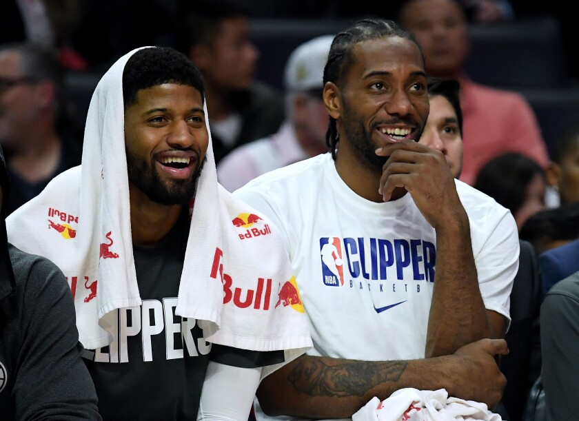 Clippers forwards Paul George, left, and Kawhi Leonard watch their teammates finish a win over the Suns at Staples Center.