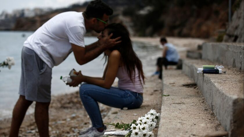 Dimitris Matrakidis kisses his sister Maria as flowers are placed at the point where a 6-month-old baby died after a forest fire in Mati, a northeast suburb of Athenson July 27, 2018.