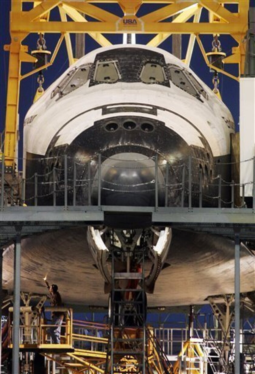 Technician Jeff Swaney, lower left, checks the thermal protection system on the underside of the space shuttle Endeavour, inside the Mate-Demate Device, as it is readied to be mounted aboard a NASA 747 for its return trip to Florida, at Edwards Air Force Base, Calif., Friday, Dec. 5, 2008. (AP Photo/Reed Saxon)