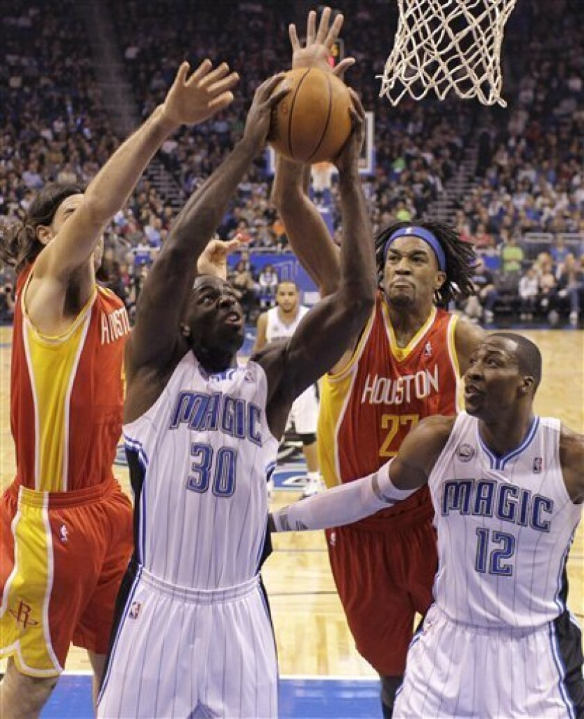 Orlando Magic's Brandon Bass (30) puts up a shot next to Dwight Howard (12) as Houston Rockets' Luis Scola, left, of Argentina, and Jordan Hill (27) try to defend during the first half of an NBA basketball game in Orlando, Fla., Friday, Jan. 7, 2011. (AP Photo/John Raoux)