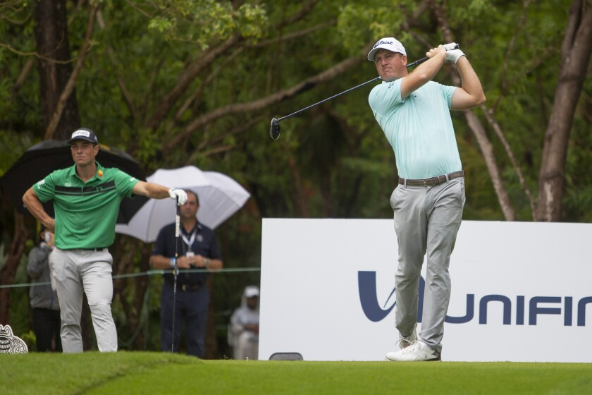 Viktor Hovland of Norway looks on as Tom Hoge of the U.S. tees off on the 1st Hole during the final round of the PGA Tour Mayakoba Golf Classic, in Playa del Carmen, Mexico, Sunday, Dec. 6, 2020. (AP Photo/Robert Fedez)