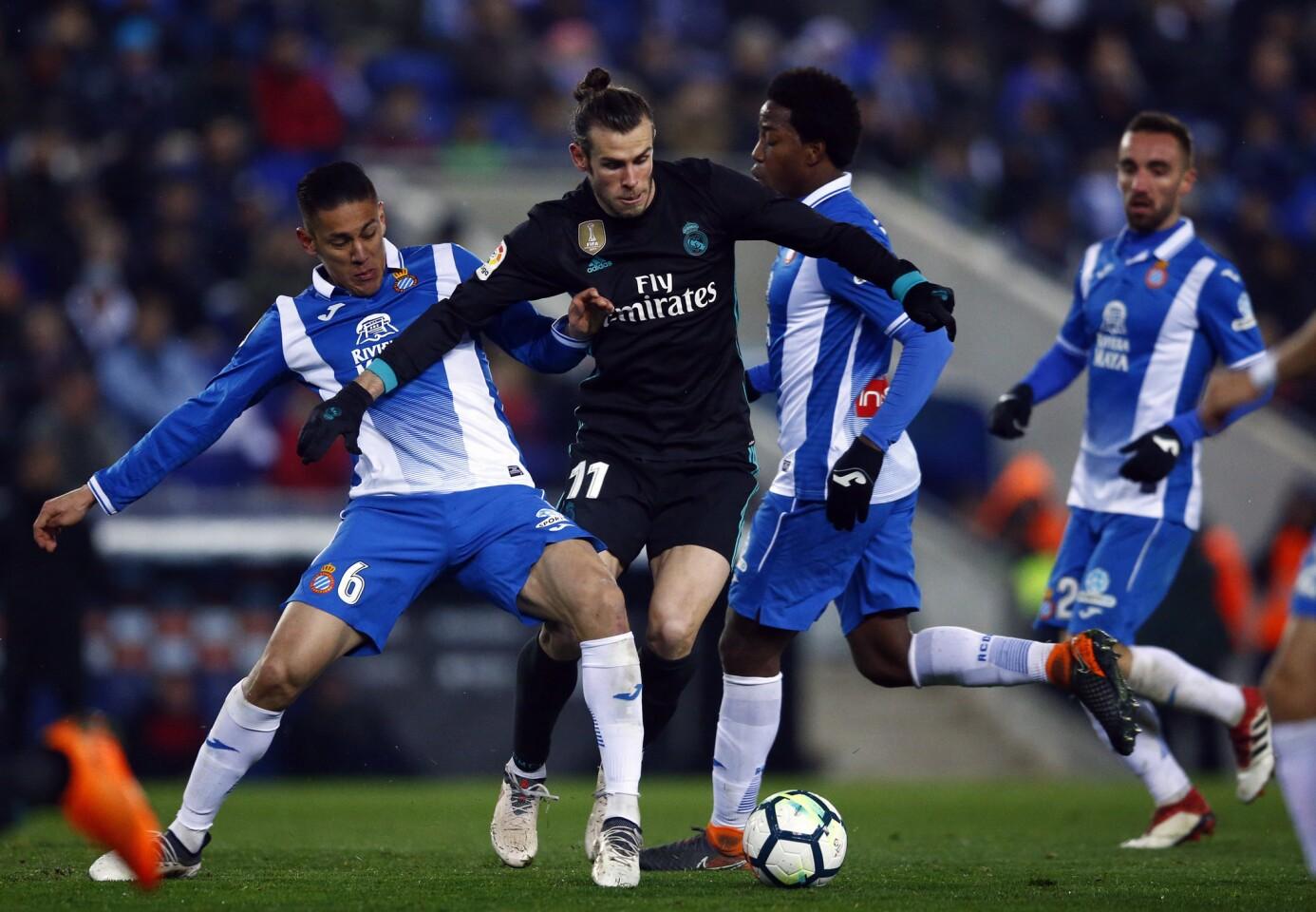 Real Madrid's Gareth Bale, center, vies for the ball with Espanyol Oscar Duarte, left, during the Spanish La Liga soccer match between Espanyol and Real Madrid at RCDE stadium in Cornella Llobregat, Spain, Tuesday, Feb. 27, 2018. (AP Photo/Manu Fernandez)