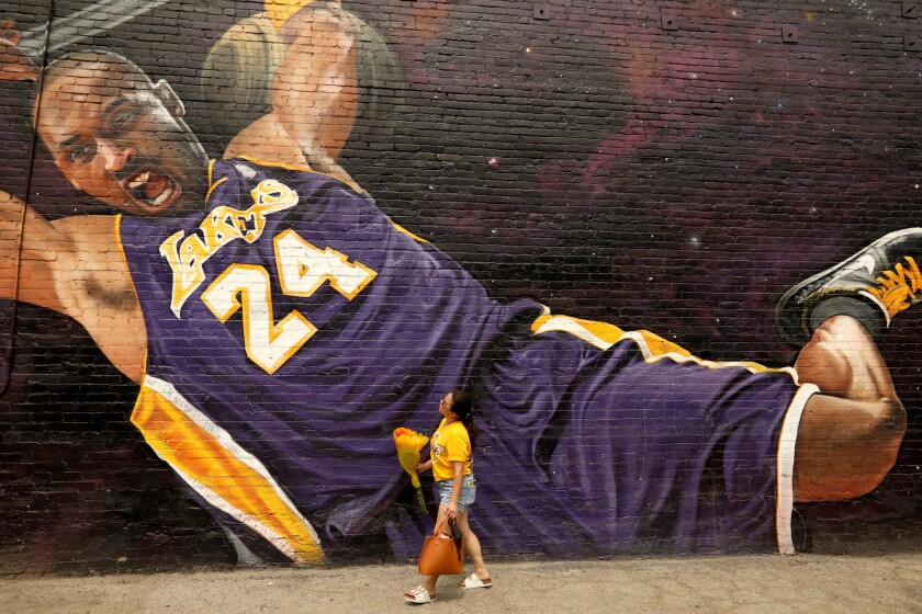"LOS ANGELES, CA - AUGUST 23, 2020 - - Elizabeth Munoz, from Huntington Park, brings flowers to leave at a Kobe Bryant mural on what would have been his 42nd birthday along Hill Street in downtown Los Angeles on August 23, 2020. Munoz, her sister and nephew, were visiting as many murals of the late Lakers star and leaving flowers to wish him a Happy Birthday. ""Thanks for all the memories. We'll never forget you,"" Munoz said. The mural was created by L.A. native artist Enkone. (Genaro Molina / Los Angeles Times)"