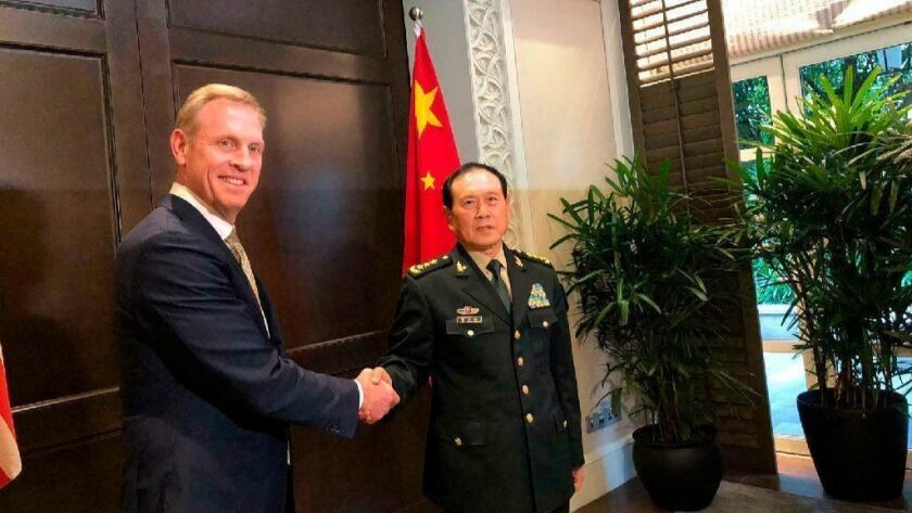 Acting U.S. Defense Secretary Patrick Shanahan, left, shakes hands with Chinese Defense Minister Wei Fenghe during a meeting on the sidelines of the 18th Shangri-La Dialogue in Singapore.