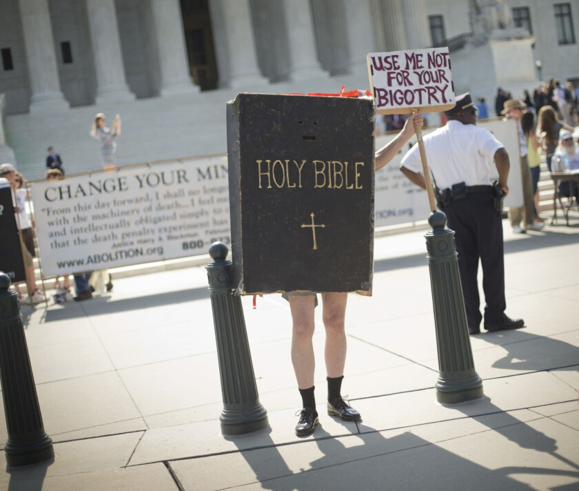 Your new health insurance guidebook? A demonstrator stands outside the Supreme Court building awaiting the Hobby Lobby ruling Monday.