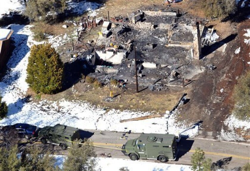 In this aerial photo, law enforcement authorities investigate the burn-out cabin Wednesday, Feb.13, 2013 where accused quadruple-murder suspect Christopher Dorner was believed to have died after barricading himself inside, during a Tuesday stand-off with police in the Angeles Oaks area of Big Bear,