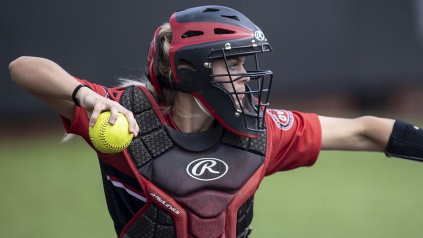 A softball catcher prepares to make a throw.