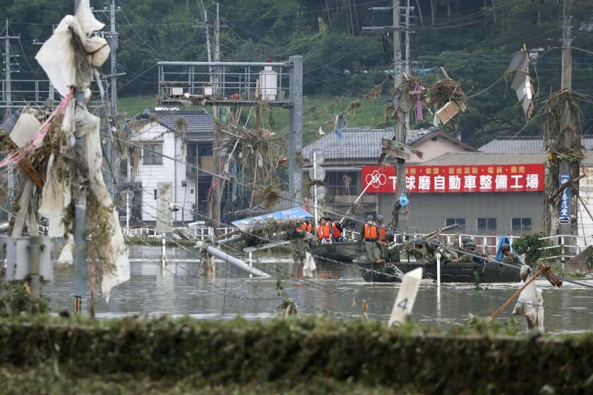 Miembros de las Fuerzas japonesas de Autodefensa trasladan en bote a varias personas para llevarlas a zonas más seguras en el pueblo de Kuma, en la prefectura de Kumamoto, en el suroeste de Japón, el domingo 5 de julio de 2020. (Kyodo News via AP)