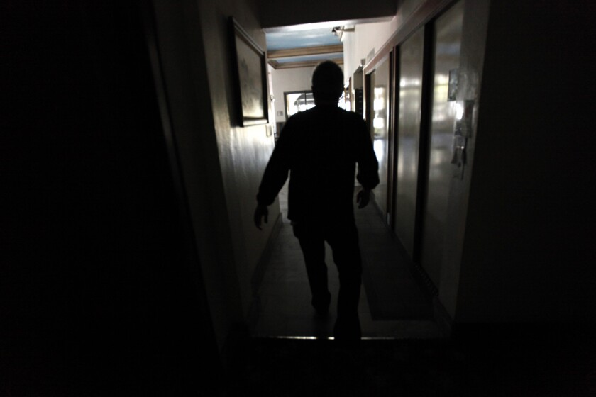 Peter DeBruyn, 70, walks down a hallway Friday at the Sovereign apartments, which were left in the dark by the power outage in Long Beach.