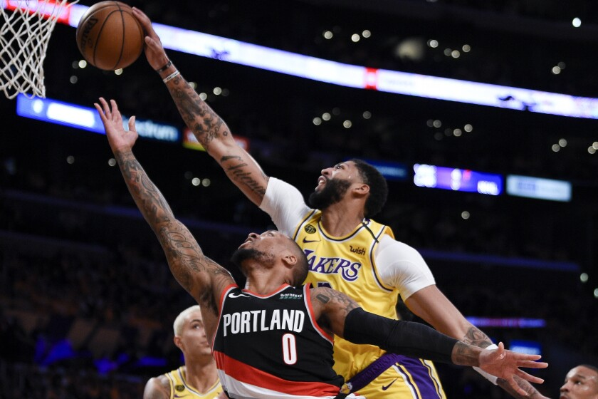 Los Angeles Lakers forward Anthony Davis, top, blocks a shot by Portland Trail Blazers guard Damian Lillard during the first half of an NBA basketball game in Los Angeles, Friday, Jan. 31, 2020. (AP Photo/Kelvin Kuo)