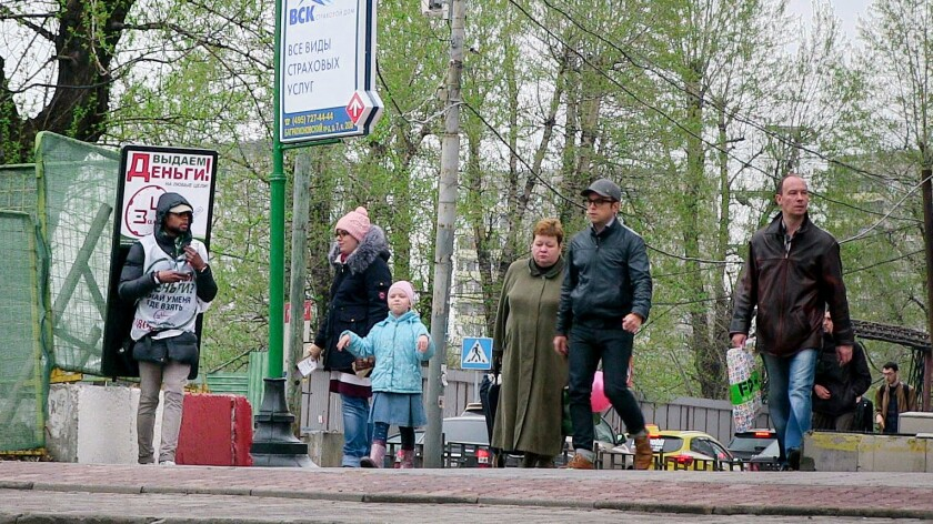 """A young man with a billboard that reads, """"Giving out money!"""" hands out leaflets advertising a payday lender in Moscow on April 27, 2016."""