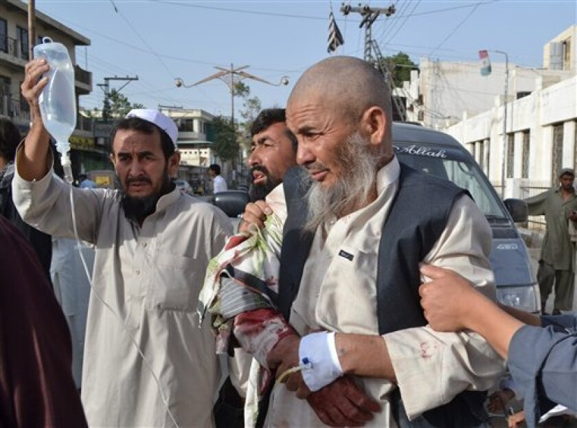 People rush an injured man to a hospital in Quetta, Pakistan on Friday, Aug. 9, 2013. Gunmen opened fire on worshippers, killing at least six people and wounded 15 in an attack on a former provincial minister outside a mosque in southwest Pakistan on Friday, police said. (AP Photo/Arshad Butt)