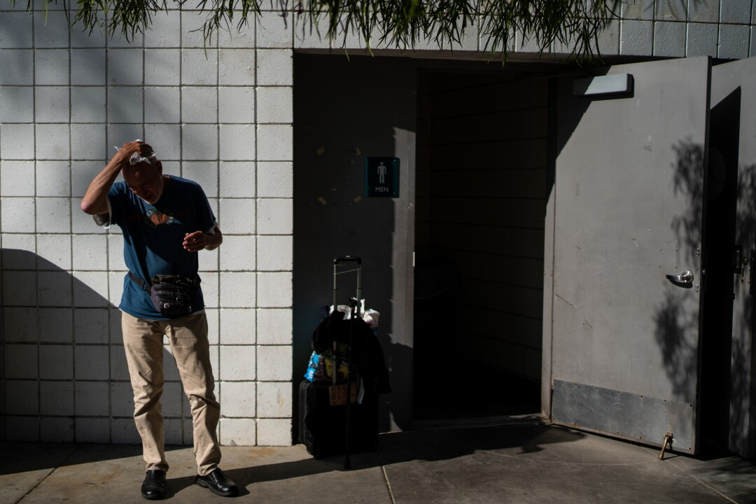 Terrance Whitten dries his face after washing it and his hands in the public restroom at Pan Pacific Park.