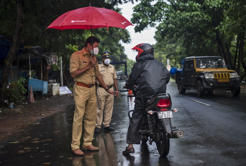 A police officer holds an umbrella to protect himself from the rain as he enforces a lockdown to curb the spread of the coronavirus in Kochi, Kerala state, India, Sunday, May 16, 2021. A severe cyclone is roaring in the Arabian Sea off southwestern India with winds of up to 140 kilometers per hour (87 miles per hour), already causing heavy rains and flooding that have killed at least four people, officials said Sunday. (AP Photo/R S Iyer)