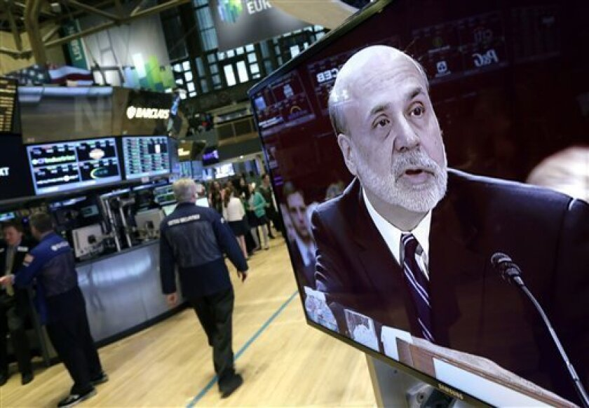 Federal Reserve Chairman Ben Bernanke is seen on a monitor on the floor of the New York Stock Exchange Tuesday, Feb. 26, 2013. The Federal Reserve's low interest-rate policies are giving key support to an economy still burdened by high unemployment,  Bernanke told Congress on Tuesday. Bernanke sign