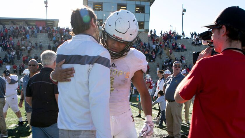 Bishop's player Amaan Banks embraces coach Joel Allen after the Knights beat Christian in the Division III final.