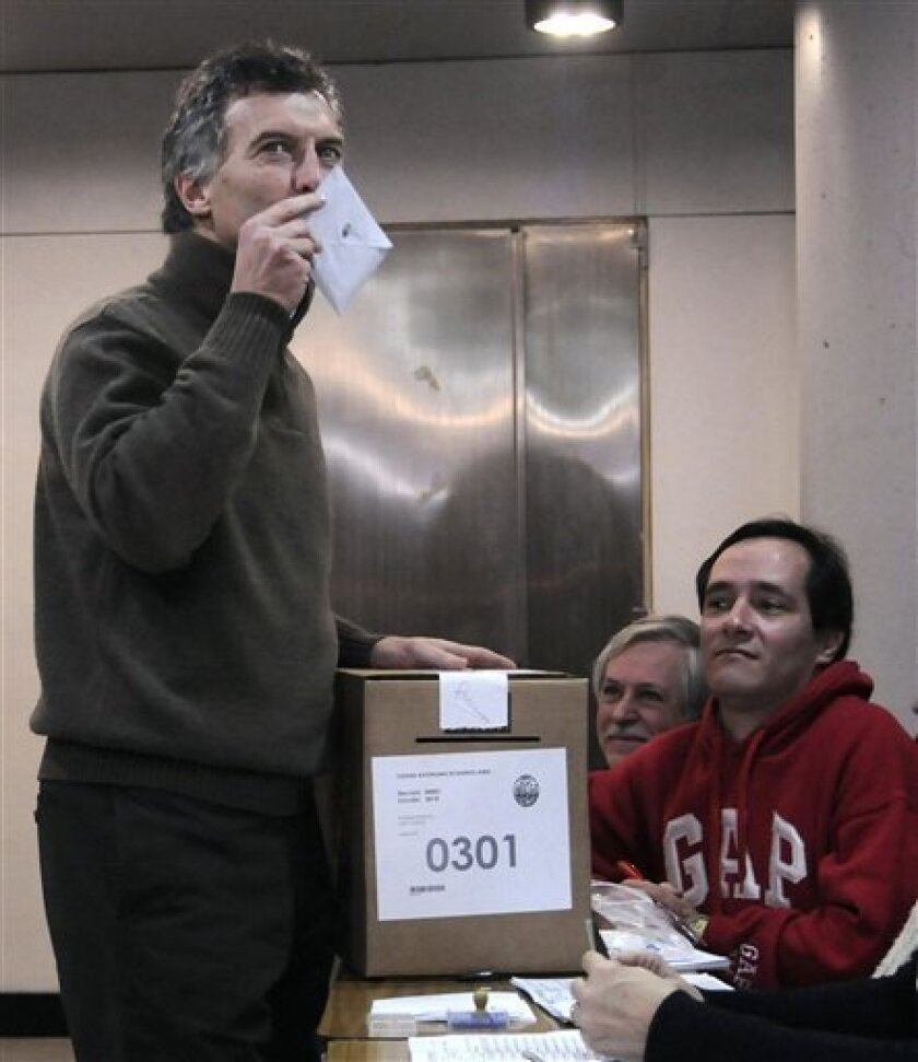 Buenos Aires' Mayor Mauricio Macri kisses his ballot before casting his vote in the mayoral election in Buenos Aires, Argentina, Sunday July 10, 2011. Macri, a conservative businessman and opponent of Argentina's President Cristina Fernandez, decided to seek a second term rather than challenge her in the upcoming presidential elections. The race for mayor in Argentina's capital was widely seen as a test of Fernandez's re-election hopes, pitting Macri against a hand-picked ally. (AP Photo/Pablo Aharonian,DyN)