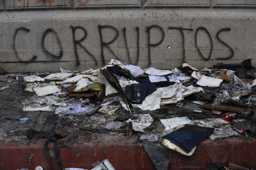 """Debris lays in front of graffiti that reads in Spanish """"Corrupt,"""" outside of the Congress building that was damaged during protests in Guatemala City, Sunday, Nov. 22, 2020. Protesters broke into the building and set it partially on fire amid growing demonstrations against President Alejandro Giammattei and the legislature for approving a controversial budget that cut educational and health spending. (AP Photo/Moises Castillo)"""