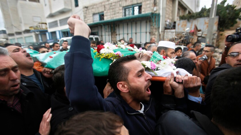 Palestinians carry the body of Abdel Fattah Sharif, who was shot to death by an Israeli soldier, during his funeral in the West Bank city of Hebron on May 28.