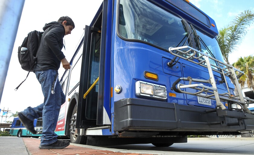 A man gets on a NCTD Breeze bus at the Oceanside Transit Center on Saturday.