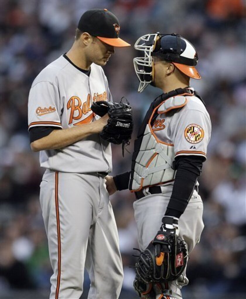 Baltimore Orioles starter Chris Tillman, left, listens to catcher Jake Fox during the third inning of a baseball game against the Chicago White Sox in Chicago on Saturday, April 30, 2011. (AP Photo/Nam Y. Huh)